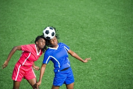 Two female soccer players competing for the ball, aerial view.