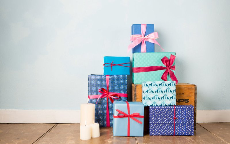 Candles and stack of wrapped christmas gifts on wooden floor